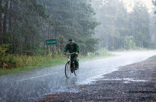 Summer Landscape - An Elderly Cyclist Riding A Country Road In The Pouring Rain, Within Tomaszow Lubelski County, Lublin Voivodeship, In Eastern Poland