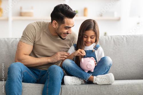 Little girl and dad saving money in piggy bank Fotobehang