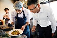 Chef Showing Garnishing To A Man