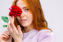 A Beautiful Girl In A Pale Pink T-shirt Poses With A Rose Flower, Covering The Half Of Her Face