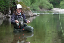 Young Woman Fly Fishing For Trout In A Clear River
