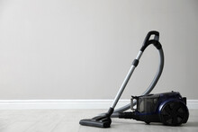 Modern Vacuum Cleaner Near White Wall Indoors, Space For Text