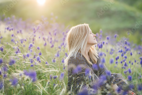 A girl in a vintage dress sits in a meadow among thickets of lilac flowers and feather grass Fototapeta