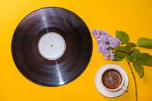Old Vinyl Record, Cup Of Coffee And Blossoming Branch Of Lilac On Yellow