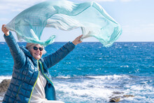 Portrait Of Senior Woman  At Sea In Windy Day, Sitting On The Cliff. Joyful Moment Appreciating Freedom And Beauty In Nature
