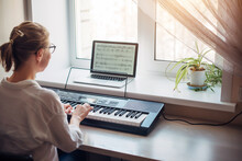View From The Back Young Woman Plays A Synthesizer, Reading Notes On A Laptop Screen. Independent Learning To Play The Piano At Home. Passion For Music, Hobbies, Leisure, Self-development.