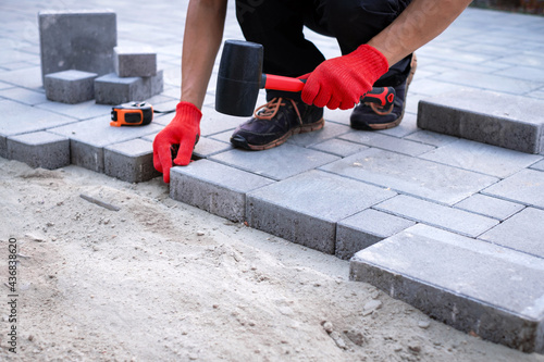 Canvas Print The master in yellow gloves lays paving stones