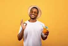 Portrait Of Positive Black Man Drinking Refreshing Cocktail, Having Beach Party, Showing Okay Gesture, Yellow Background