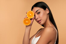 Portrait Of Asian Girl With Shining Clean Skin Of Face Holding Orange Halves In White Underwear Isolated On Beige Background. Vitamin C Cosmetics Concept