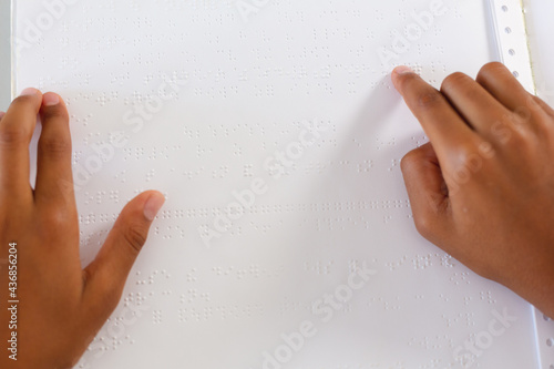 Hands of blind african american schoolboy reading braille book with fingers