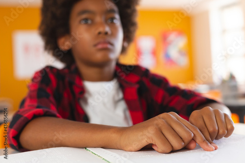 Blind african american schoolboy sitting at desk in classroom reading braille book with fingers