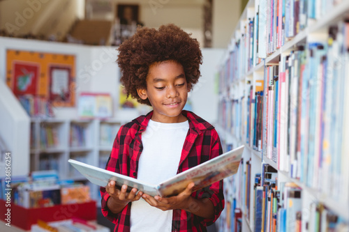Smiling african american schoolboy reading book standing in school library