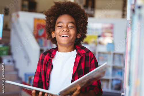 Laughing african american schoolboy reading book standing in school library