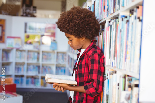 Happy african american schoolboy reading book standing in school library