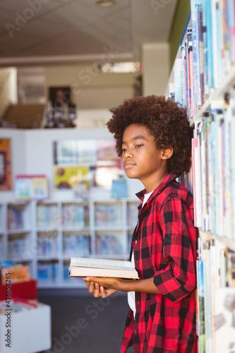 Happy african american schoolboy reading book standing in school library, looking away