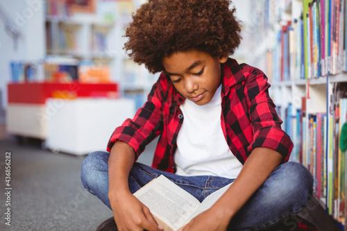 Happy african american schoolboy reading book sitting on floor in school library