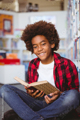 Portrait of smiling african american schoolboy reading book sitting on floor in school library