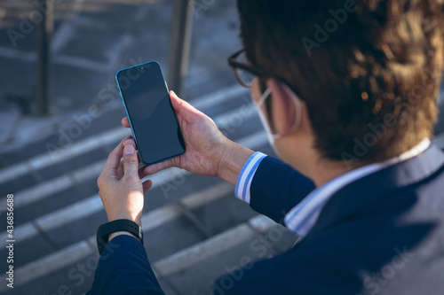 Asian businessman wearing face mask using smartphone sitting on steps in city street