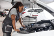 Afro Car mechanic woman is examining under hood of car at repair garage, wearing overalls, looking confident and concentrated. Side view on female trying to solve the problem of inoperative engine