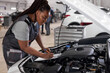 african Female mechanic in overalls at work, checking car hood writing notes in tablet while standing in auto repair service center, side view