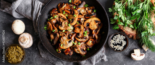 Obraz na plátne Roasted mushrooms with onion in frying pan on a dark background