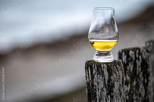 Valokuva Tasting of dram single malt scotch whisky on seashore in Scotland, old wooden po