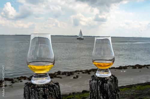 Fotografie, Obraz Tasting of dram single malt scotch whisky on seashore in Scotland, old wooden po