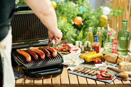 table with electric grill and grilled sausages Fototapet