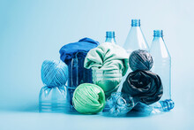 Empty Plastic Bottle And Various Fabrics Made Of Recycled Polyester Fiber Synthetic Fabric On A Blue Background