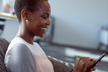 Smiling African American Businesswoman Sitting In Armchair, Using Smartphone