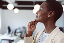 African American Businesswoman Thinking, Touching Chin At Work