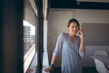Caucasian Businesswoman Standing At Window, Talking By Smartphone At Work
