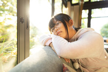 Portrait Of Thoughtful Asian Girl In Glasses Sitting On Sofa