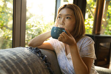 Portrait Of Asian Woman Drinking Tea And Sitting On Sofa