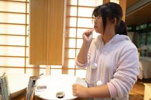 Asian Girl In Glasses Brushing Teeth In Bathroom