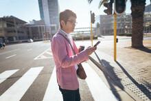 Asian Businessman Using Smartphone Drinking Takeaway Coffee Crossing City Street