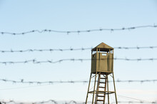 The Old Wooden Watchtower Behind The Barbed Wire Fence