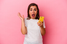 Middle Age Caucasian Woman Holding Mobile Phone Isolated On Pink Background Surprised And Shocked.