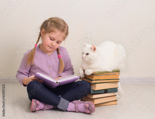 Fotografia, Obraz Little smiling girl sitting on the floor with her cat and reading a book