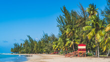 Red Life Guard Hut And Palm Trees On Tropical Beach. Luquillo Beach, Puerto Rico