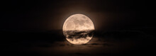 Horizontal Panoramic Image Of The Full Moon Slightly Obscured By Clouds During The Night