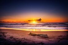 O Nascer Do Sol Numa Praia Bem Bonita Com Poucas Nuvens No Céu E Uma Visão Um Pouco Panorâmica.