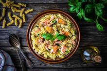 Fusilli With Roasted Salmon On Wooden Table
