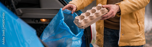 Fotografie, Obraz cropped view of man holding carton container near blue trash bag in car, banner