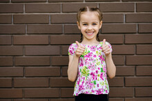 The Little Girl Smiles And Shows Two Thumbs Up. A Beautiful Child Stands Against The Background Of A Brick Wall With A Place For Text. Emotional Girl Is Dressed In Bright Clothes And Is Very Happy