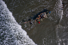Aerial View Of A Few People Pushing A Traditional Canoe Along The Shoreline On St. Martin's Island, Teknaf, Chittagong, Bangladesh.