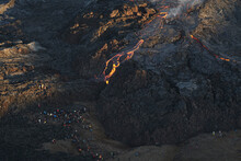 Aerial View Of A Group Of Tourist Enjoying An Excursion Along A Vulcano, View Of Magma Streaming Down The Mountain Ridge, Grindavík, Southern Peninsula, Iceland.
