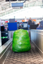 Backpack Is Wrapped In Green Plastic Wrap Weighed At Check-in Counter Before Departure At Prague Airport. Concept Of Safe Travel, Luggage Security. Plastic Pollution
