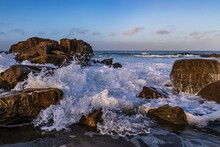 Closeup Of Foamy Wave Rushing Ashore Amid Rockly Coast Of Laguna Beach, California. Early Morning Sky, Clouds In The Distance.