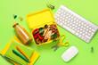 Leinwandbild Motiv Lunch box with tasty food and school stationery on color background